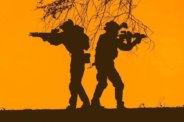 夕焼け空の兵士チームのシルエット。機関銃パトロールの兵士