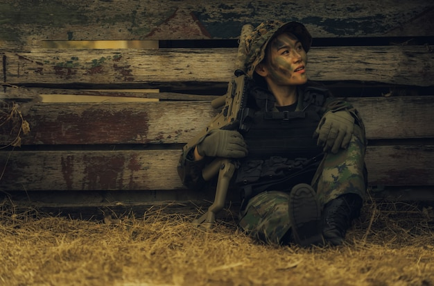 Девушка армии при винтовка сидя в лесе на поле битвы.