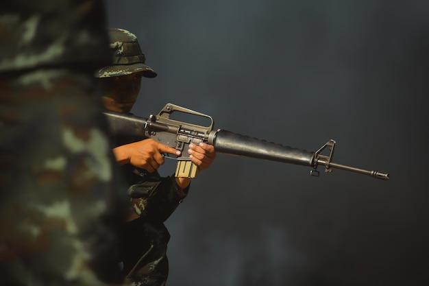 Солдат армии в защитной форме держит винтовку. штурмовая винтовка солдата спецназа с глушителем.