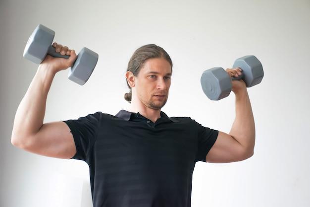 男性トレーナーがフィットネスで運動する方法を教えています。