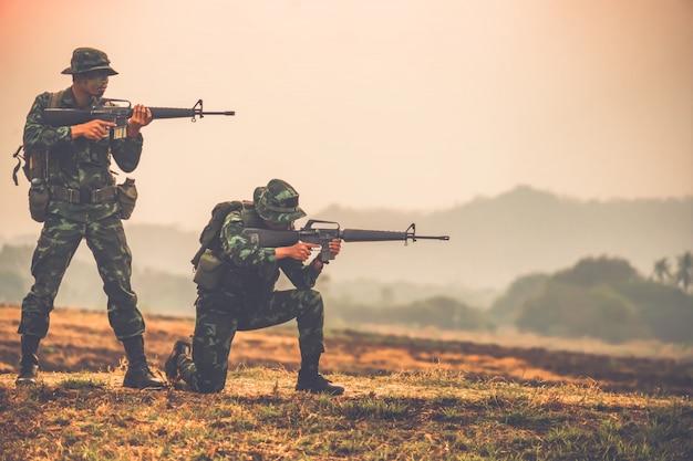 Силы специального назначения команды. солдат штурмовая винтовка с глушителем. солдаты действия силуэта держат оружие. военные и концепция опасности.
