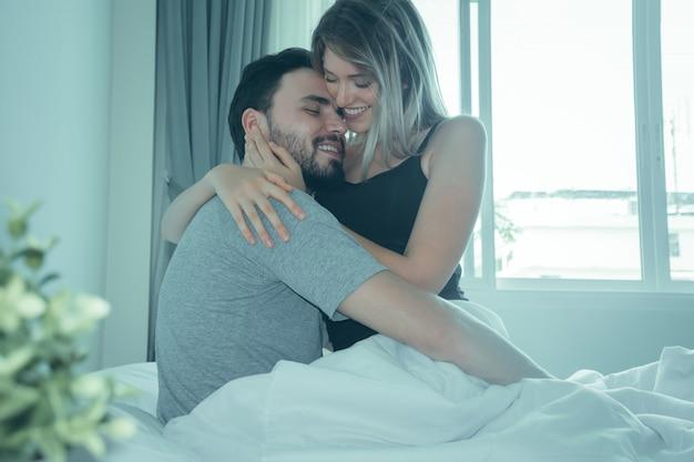 Влюбленная пара, поцелуи в постели. счастливая пара, лежа вместе в постели.