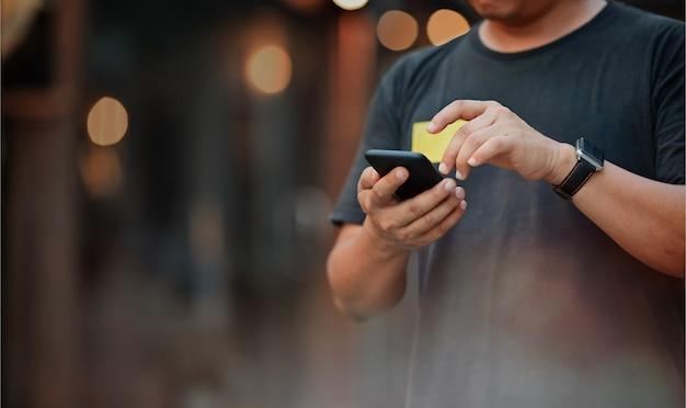 通りの夜に携帯電話を使用している人。
