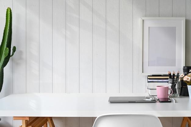 スタイリッシュなワークスペースのラップトップ、ポスター、ホームオフィス用品、コピースペース。
