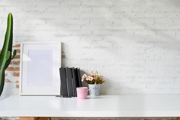 マグカップとオフィス用アクセサリーの白い木製の机の上のモックアップポスター