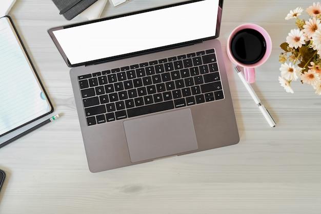 Офисный ноутбук с кружкой кофе, блокнотом и канцелярскими товарами