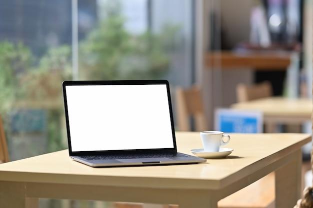 カフェのバックグラウンドでテーブルの上のモックアップの空白の画面のノートパソコン。