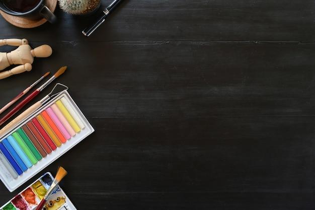 暗い木製のテーブルの上の創造的なアクセサリーとアーティストのワークスペースの色。ワークスペースとコピースペース。