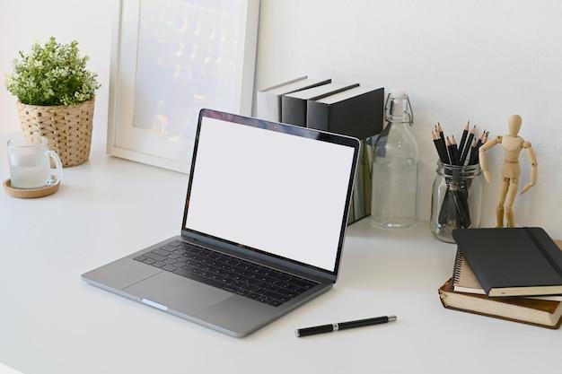 白い作業机の上のノートパソコンをモックアップします。
