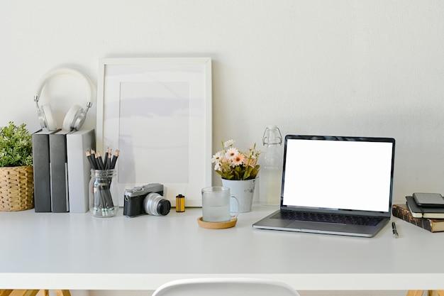 白いテーブル、クリエイティブワークスペース上のラップトップをモックアップします。