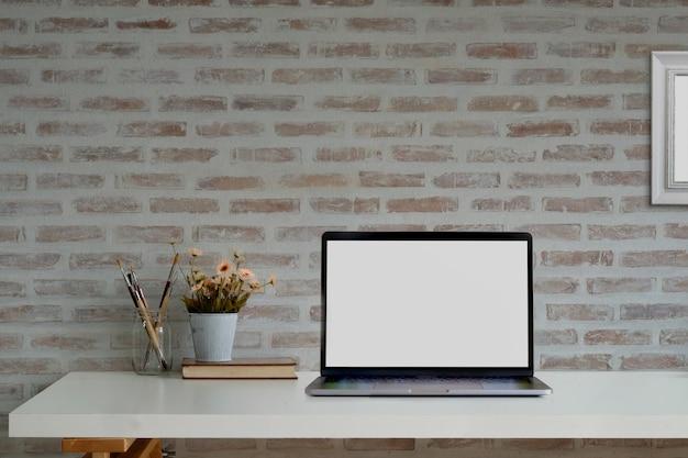 モックアップ空白の画面のノートパソコンと消耗品のロフトワークスペース。