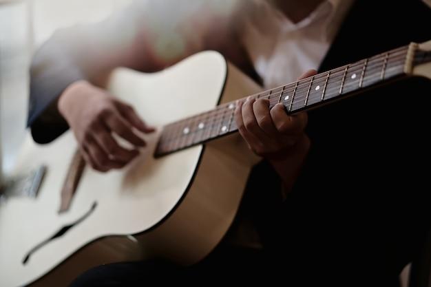 アコースティックギターを弾く練習をした男性のトリプルショット