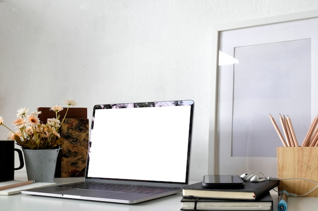 Макет чердак рабочей области, пустой экран ноутбука и макет плаката на белом столе.