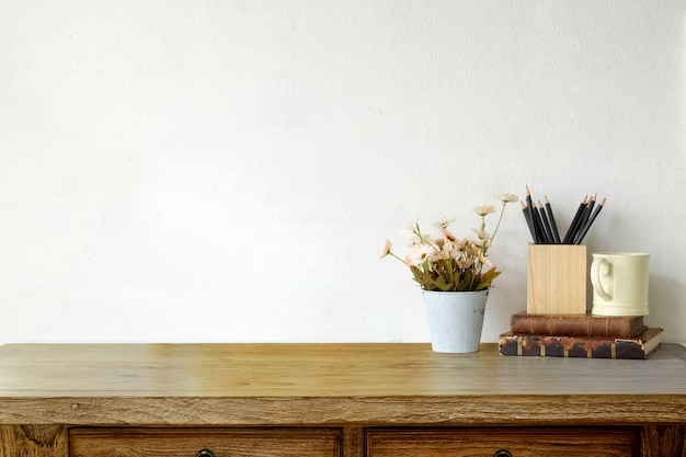 ビンテージの本、コーヒーのマグカップ、花とロフトの木製の机。ワークスペースとコピースペース