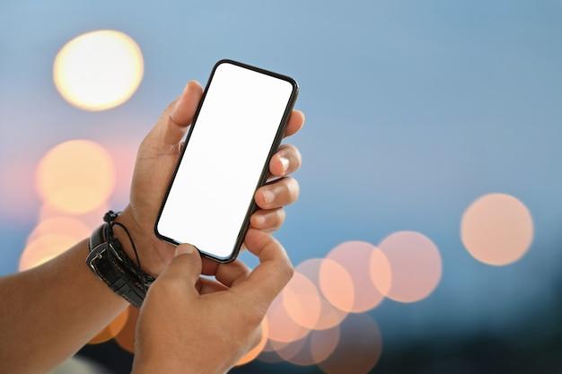 夜のボケ味の光の上に空白の画面携帯電話を持つ男の手