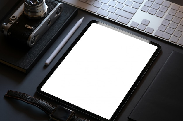 暗い革張りの机の上の空白の画面タブレットとオフィス企業のモックアップデザイン