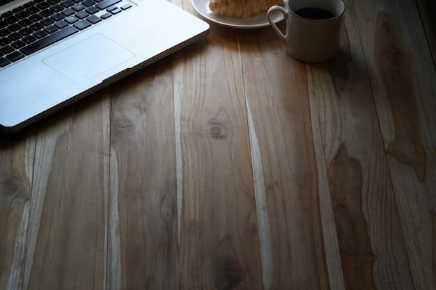 Макет настольного ноутбука, кофе и круассан на деревянный рабочий стол.