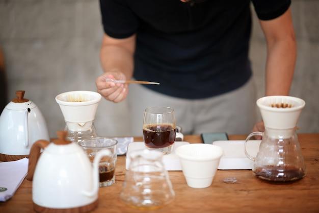 ドリップコーヒーとテーブルの上のアクセサリーを作るバリスタ
