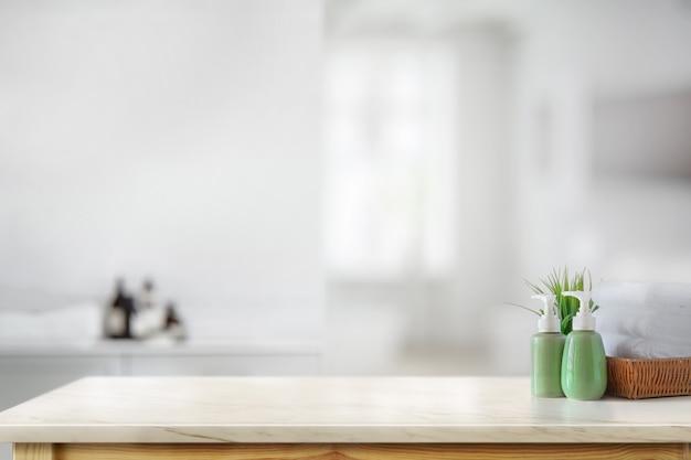 Керамическая бутылка-шампунь с белыми полотенцами на мраморной стойке на фоне ванной комнаты
