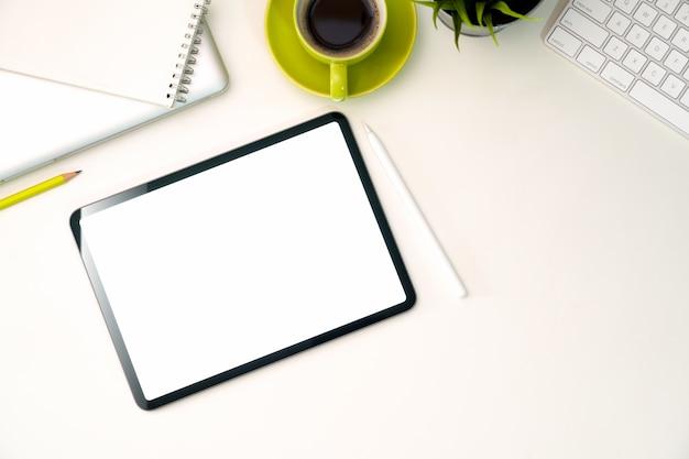 空白の画面のオフィスのワークスペースにタブレットをモックアップ
