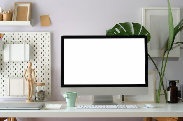 空白の白い画面を示すロフトワークスペーステーブル上のコンピューターをモックアップします。