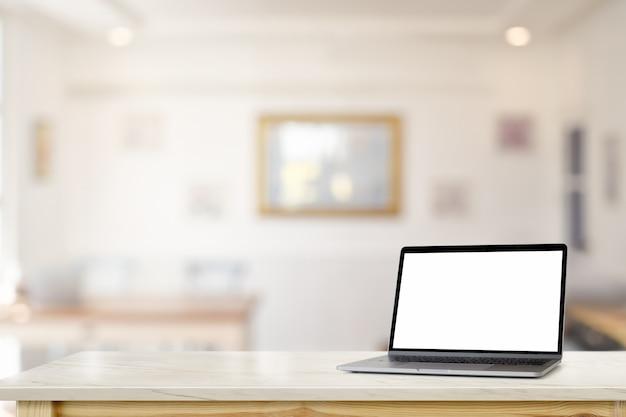 リビングルームの上の大理石の机のテーブルの上の空白の画面ラップトップをモックアップします。