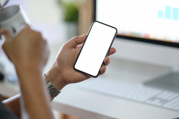 ビジネスの男性がオフィスで空白の画面携帯電話を表示