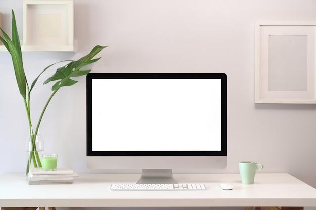 空白の白いスクリーンコンピューターとロフトクリエイティブワークスペースをモックアップします。