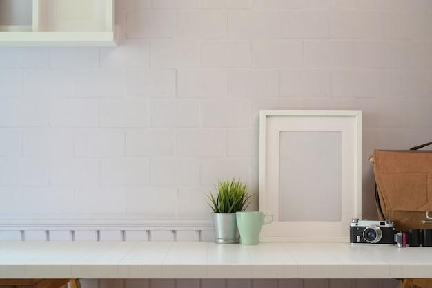 白い木製の机の上のスペースとコピースペースに有利なカメラのモックアップポスター。