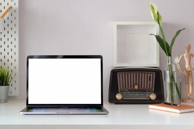 ノートパソコン、ポスター、ビンテージラジオ、空白の画面をモックアップでロフト職場