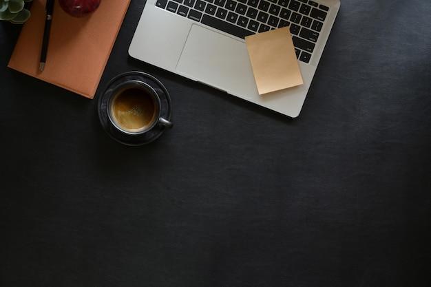 暗い革のデスクトップ上のオフィスのガジェットを持つノートパソコン