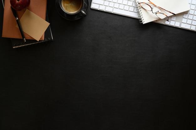 Темный кожаный офисный рабочий стол с канцелярскими товарами