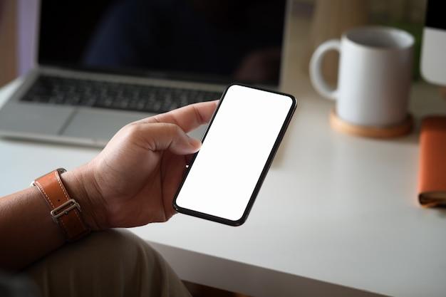 空白の画面がオフィスで男の手で携帯電話をモックアップ