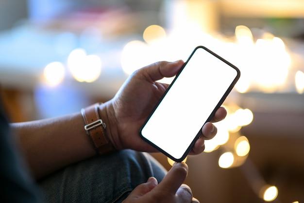 背景をぼかした写真の通りの夜にモバイルのスマートフォンを抱きかかえた