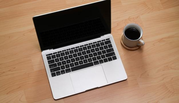 ノートパソコンと木製の机の上のコーヒーをモックアップします。