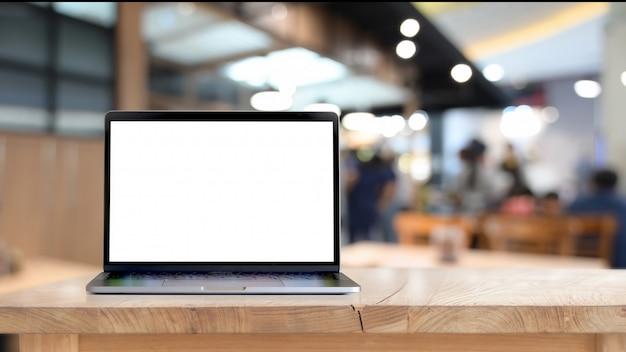 木製のテーブルに空白の画面のラップトップをモックアップします。