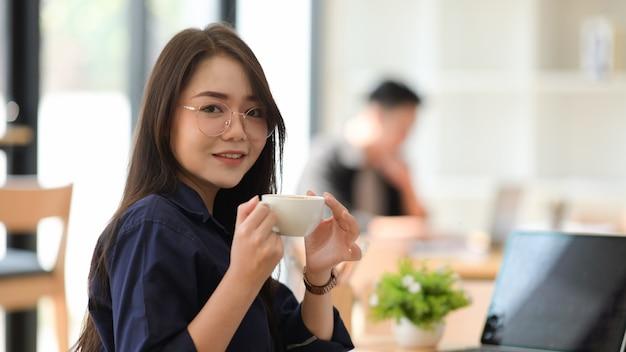 アジアの女性がオフィスでコーヒーを飲む