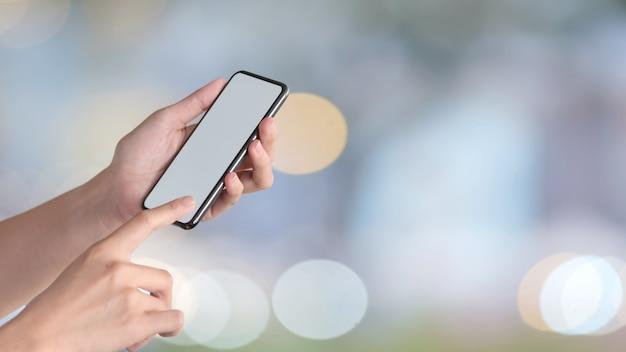 Женщина держит мобильный телефон и показывает пустой экран для графического монтажа