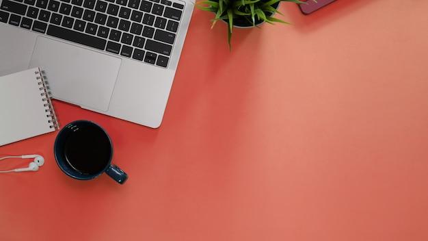 事務用品とオレンジ色の背景上のラップトップのオフィスデスクテーブル