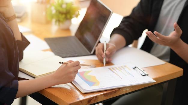 デジタルタブレットと紙を使用するビジネスマンが一緒にオフィスで働く