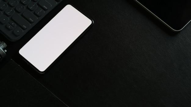 暗いオフィスの机の上の空白の画面携帯電話とオフィスアクセサリーをモックアップします。