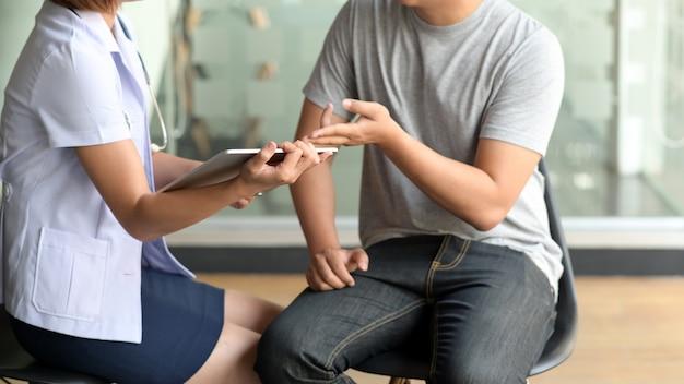 Женский доктор показывая цифровую таблетку к пациенту