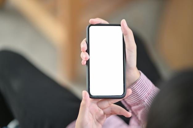 空白の画面を持つ黒い携帯電話を両手のイメージ
