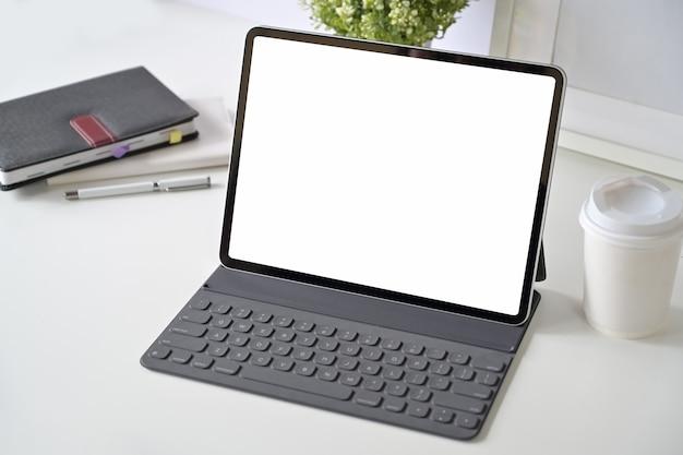 ワークスペースのテーブルにスマートキーボードでモックアップ空白画面タブレット。