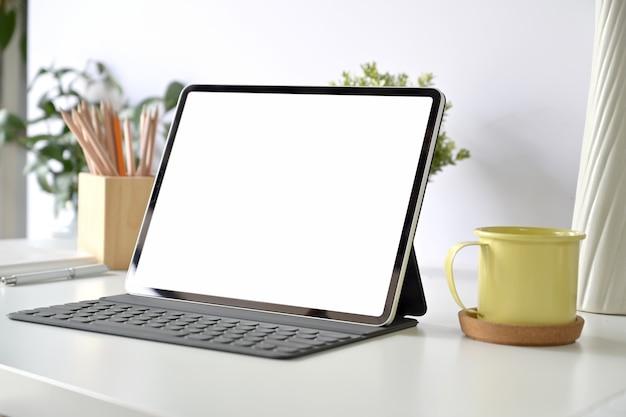 空白の画面のタブレットと白いテーブルの上のスマートキーボードのモックアップ