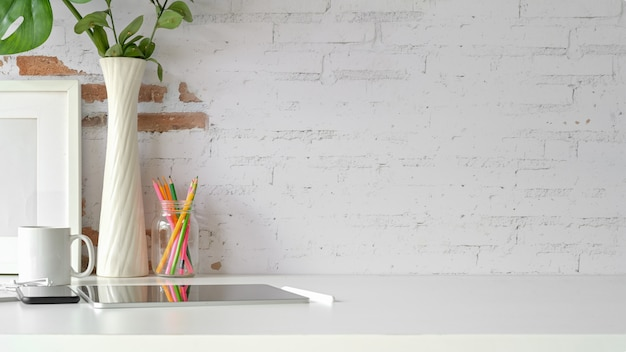 ロフトワークスペースの白いテーブルに職場、コピースペース、タブレット、モックアップポスターの正面図。