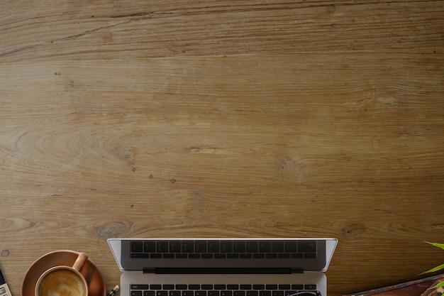 ビジネス静物ノートパソコン、一杯のコーヒーと供給の木製オフィスデスクテーブル。