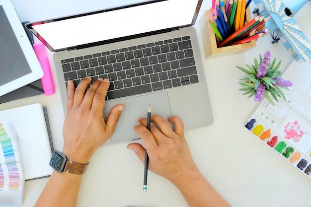 若いデザイナーが机の上のノートパソコンで作業します。