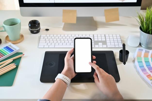 スタジオの職場でモバイルスマートフォンを保持して使用するクリエイティブデザイナー