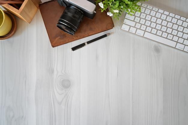 事務用品とコピースペースを持つ木製オフィスデスクトップの上から見たショット